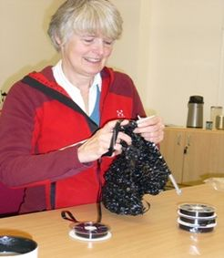 woman knitting with video tape