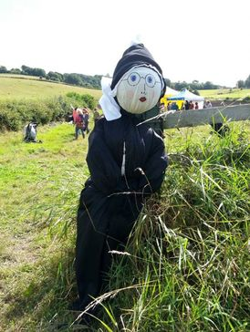 a scarecrow by a field gate wearing a black dress and hoof