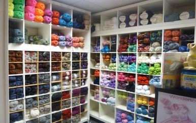 balls of knitting wall all colours on shelves