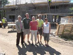 group of people standing outside a new house under construction