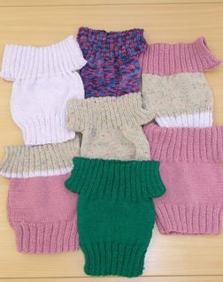 many baby jumpers in coloured wool