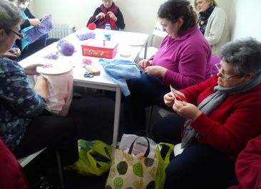 group of women knitting round central table
