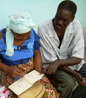 African man and woman examine record of savings