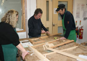 man and woman in woodwork class