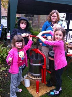 three children by the brightly coloured apple press