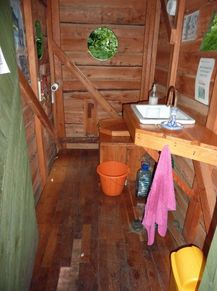 inside a wooden hut with toilet and sink