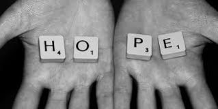 "scrabble letters on hands spelling ""hope"""