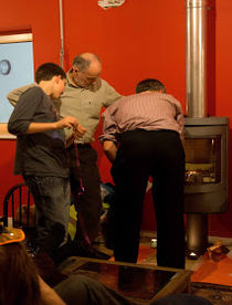 two men and a youn lad attend to a wood burning stove