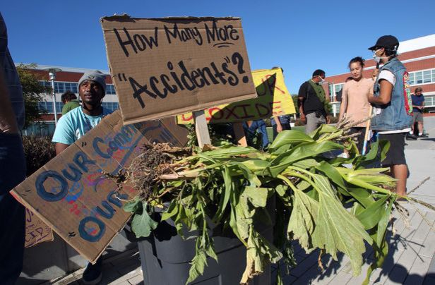 Members of Urban Tilth take their contaminated vegetables to a Chevron community meeting.