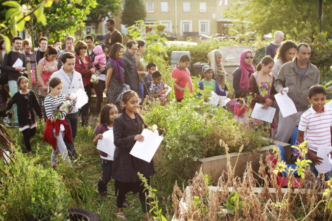 The Edible Garden: The grand entry for a celebratory feast of The Edible Garden. In partnership with East End Women's Institute, Mile End Park and local daughters, mothers and grandmothers, artists, chefs and gardeners to grow an edible garden. Produced by Phakama. Photo by Caroline Gervay.