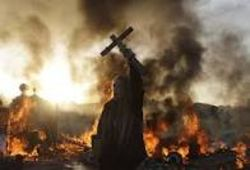 An Irish traveller Dale Farm resident holds up a crucifix against a backdrop of burning barricades