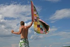 man waving patchwork quilt