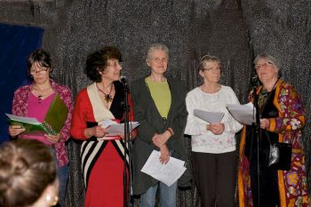five women in a row standing behind microphones holding papers in their hands
