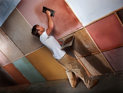 Adam plastering patches of different clay plasters.