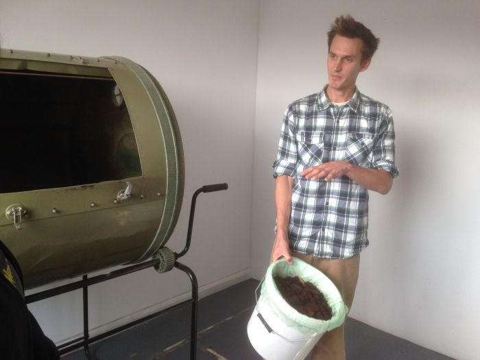 Adam with the compost tumbler in which the innoculant and the coffee grounds are combined.