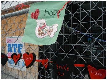 Crafted hearts adorn a fence outside a damaged building in Lyttelton, 2012. Image Credit: Zack Dorner