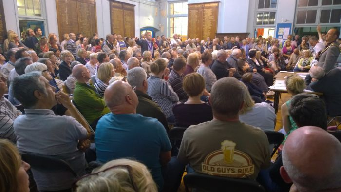 A meeting organised by the town council with over 400 attendees, held in the former grammar school, now run as a community centre by volunteers.