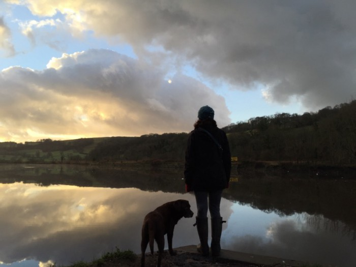 Fiona and her dog Rosie by the River Dart at sunset.