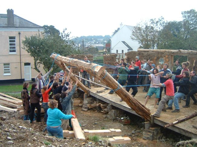 Cedar frames made from trees felled directly over the road from the college, being raised into position.