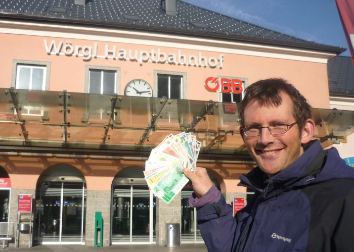 The author displaying his collection of local currency notes outside Worgl train station in 2009.